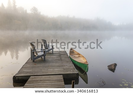 A green canoe tied to a wooden dock with a pair of empty Adirondack chairs - Haliburton Highlands, Ontario, Canada