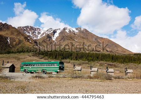 A green shuttle bus parked between the toilets at Toklat river rest stop of Denali National Park and Preserve.
