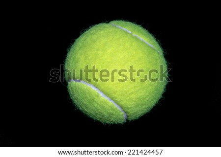 A green tennis ball isolated on black background