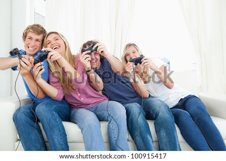 A group of friends leaning to the side as they play video games together.