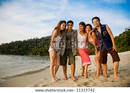 a group of male and female friends by the beautiful tropical beach