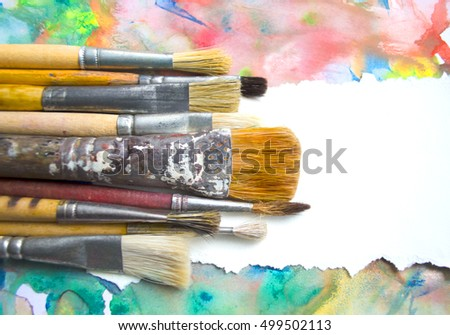 A group of paintbrushes on abstract colorful watercolor background with place for text. Can be used for background, banner, poster, advertising workshops. Blank for motivating quote, note, message.