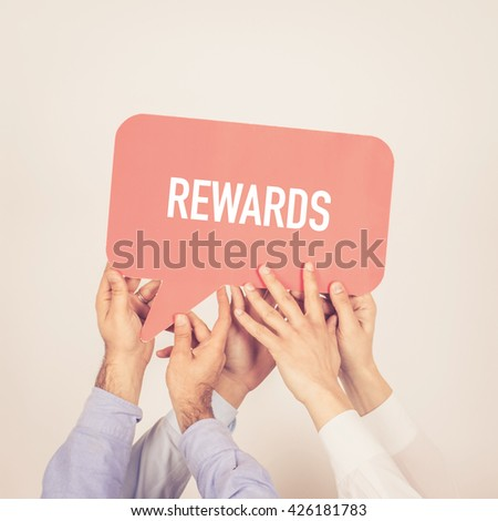 A group of people holding the Rewards written speech bubble