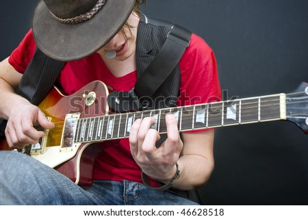 A guitarist improvising with a plectrum in his mouth