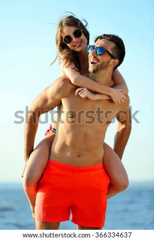 A guy carrying a girl on his back, at the beach, outdoors