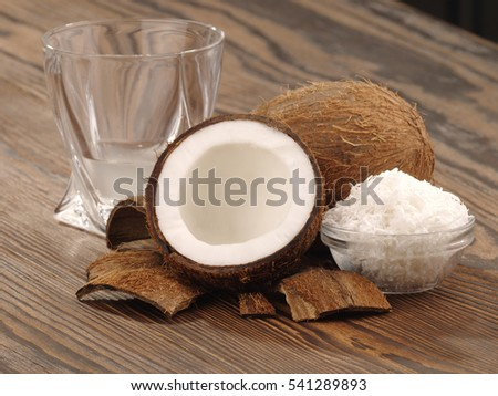 a half of a coconut and glass with coconut juice on a wooden table