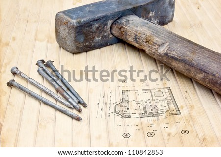 A hammer and nails lying on bamboo with blueprint next to ut. Construction industry or home construction business.
