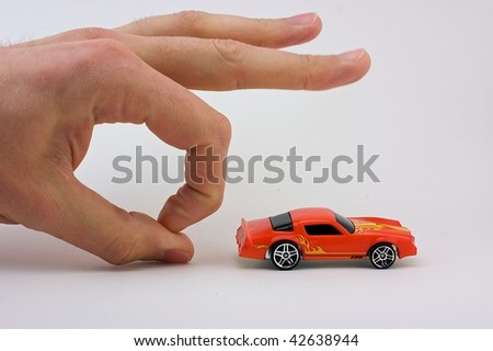 A hand flicks a toy car
