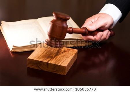 A hand holding a gavel and a book lying on the table