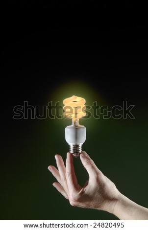 A hand holds a lit compact florescent light bulb. The bulb gives off a warm glow. Green background fades to black with space for copy.