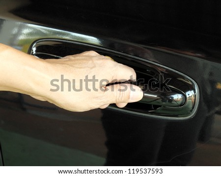 a hand is going to pull a car's door handle