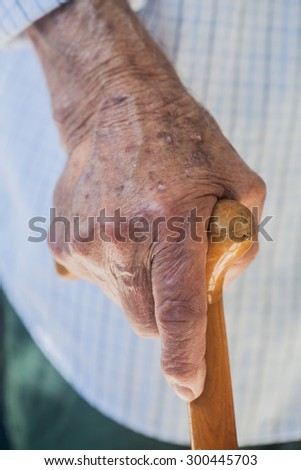 a hand of an elderly man holding a wooden walking stick with a light background