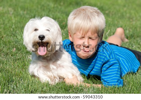 A handsome boy and his white dog are lying on the green meadow with their pink tongues out