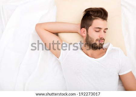 A handsome young adult man sleeping in bed.