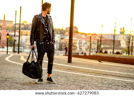A handsome young hipster man standing next to a tramline and looking around