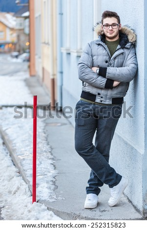 a handsome young man with winter clothes strolling in a small mountain town in europe