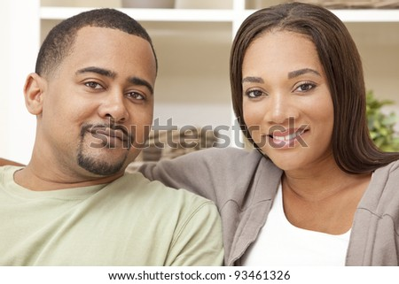 A happy African American man and woman couple in their thirties sitting at home