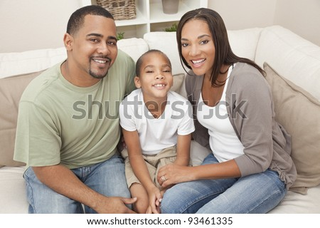 A happy African American man, woman and boy, father, mother and son, family sitting together at home