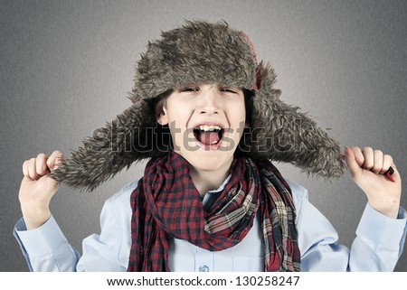 A happy boy in a cap and a scarf