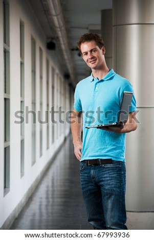 A happy college guy in blue collared shirt arm akimbo holding a laptop standing in a beautiful university campus corridor.  Tall handsome British male caucasian looking at camera head cocked