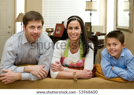 A happy mother, father and young son in their comfortable home.