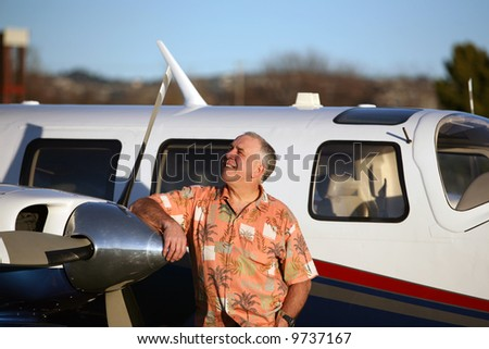 a happy, smart and well to do man stands proudly next to his latest airplane and looks to the sky to decide if he wants to fly to paris for French Fries