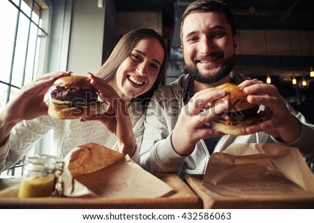 A happy smiling woman and a handsome bearded man are enjoying their delicious and tasty burgers in the burger-bar