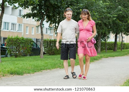 a happy young pregnant woman with her husband walking in a park