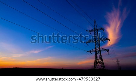 A high voltage power pylons against blue sky and sun rays.