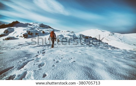A hiker and their dog out walking in snow covered mountains, UK. Added film grain and colour styling.