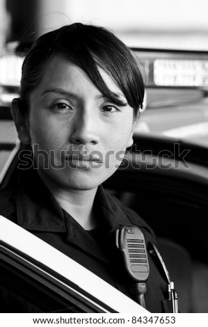 a Hispanic female police officer looking serious while standing at her patrol car.