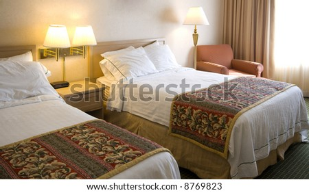a hotel room with two beds, lamps, pictures chairs and pillows