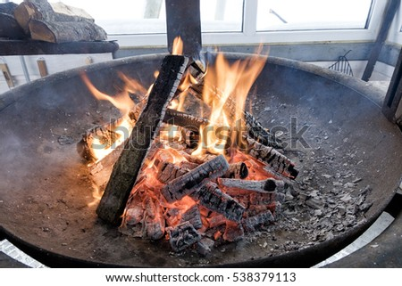 a huge bowl of barbecue with burning it with fire and hot coals