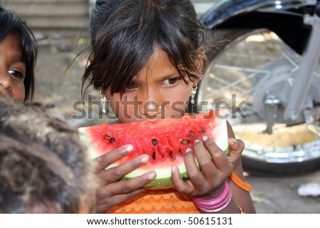 A hungry street-side Indian girl eating a watermelon.