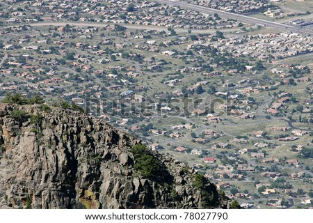 A jagged mountain abuts and limits urban sprawl in the arid southwestern desert , USA