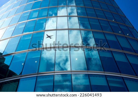 A jet airplane silhouette with business office towers background, London