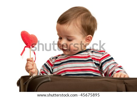 A kid is taking his first valentine out of the suitcase; isolated on the white background