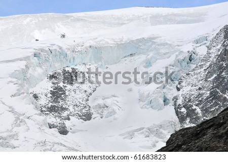 A large piece of glacier has weakened broken away from this mountain side leaving ice cliffs due to global warming