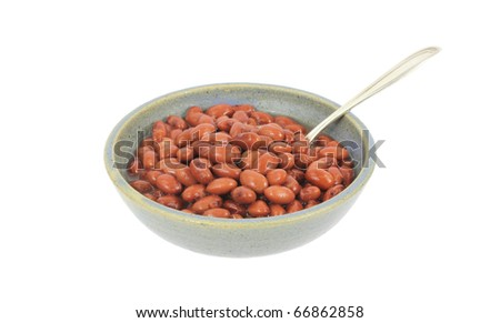 A large serving of pink beans with spoon in and old bowl on a white background.