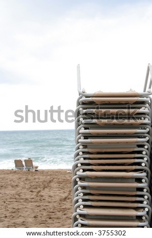 a large stack of beach chairs on the beach