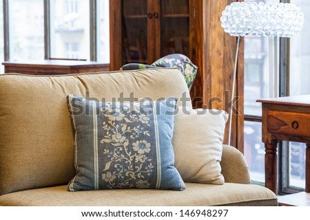 A light brown sofa with a cream and a blue pillow with flowers