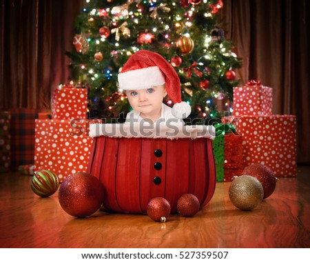 A little baby is sitting in a red basket by a Christmas tree with lights and presents in the home for a family holiday concept.