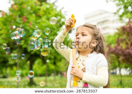 A little beautiful girl plays with soap-bubbles