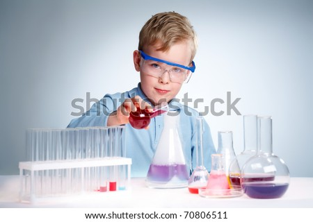 A little boy pouring liquid into a flask and looking at camera
