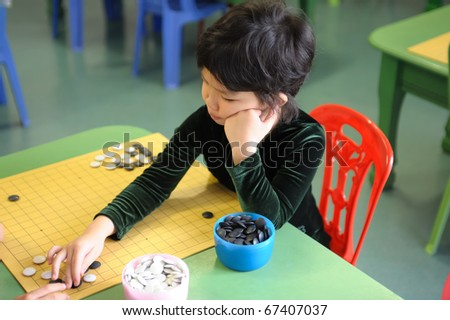 A little chinese kid learning to play go(weiqi) game