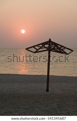 A lone umbrella on the background of sea, sky and sun.
