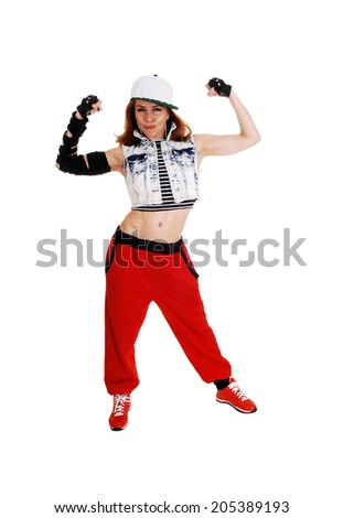 A lovely woman in red pants, jeans jacket and a hat standing with her arms lifted up, isolated on white background.