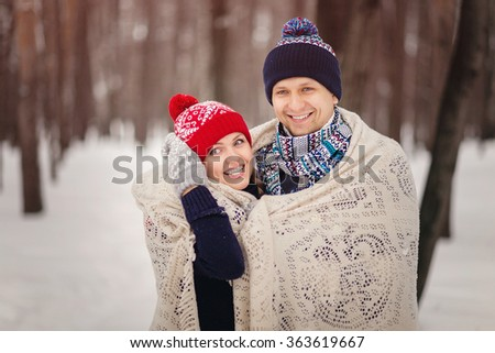 A loving couple walking in winter park. Lovers covered a blanket, cuddling. Valentine's Day, Christmas. Wearing colorful scarves and hats.