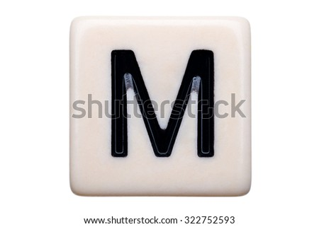 A macro shot of a game tile with the letter M on it on a white background.