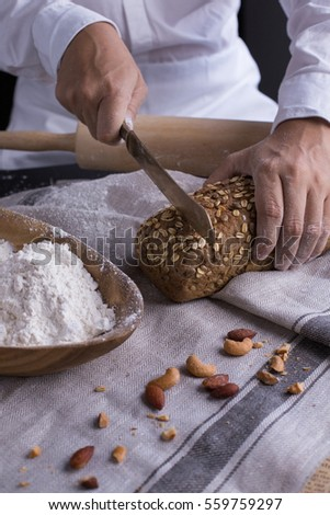 A male chef's hand present and cutting whole grain bread with gold knife and pouring flour.